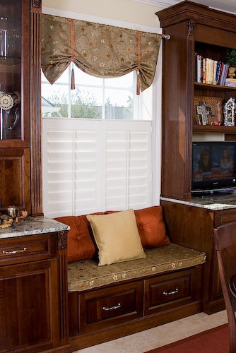 kitchen sitting nook window seat with dark cabinets and plantation shutters on window | Marchand Creative Kitchens Cabinets New Orleans Metairie Mandeville LA