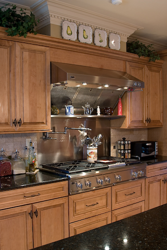 stainless hood, range water spout with light wood cabinets | Marchand Creative Kitchens Cabinets New Orleans Metairie Mandeville LA